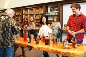 group of people standing around a counter with moonshine