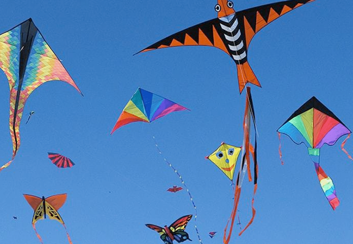 kites flying in a cloudless blue sky