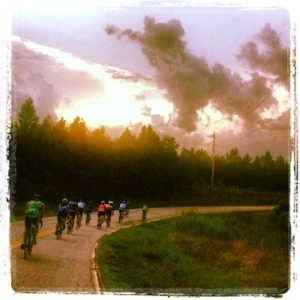 cyclists riding at sunset