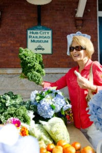 woman holding a big bunch of kale and smiling