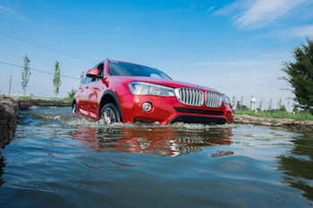 red bmw driving through water