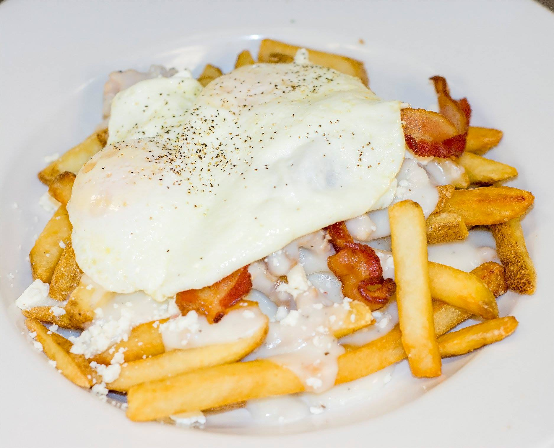 french fries topped with white gravy, bacon, feta, and eggs