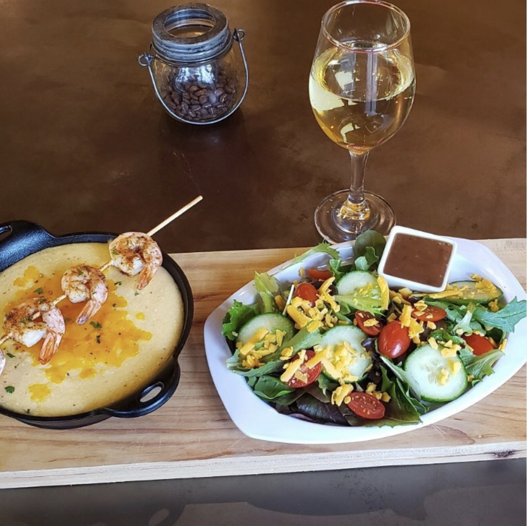 cork and beans chorizo shrimp and grits with a glass of wine and side salad