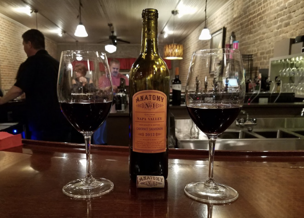 two glasses of wine surrounding a bottle of wine